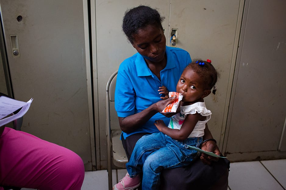 Lunie's mother, Gertha Morette, feeds her daughter therapeutic food during their first malnutrition visit in April 2016.