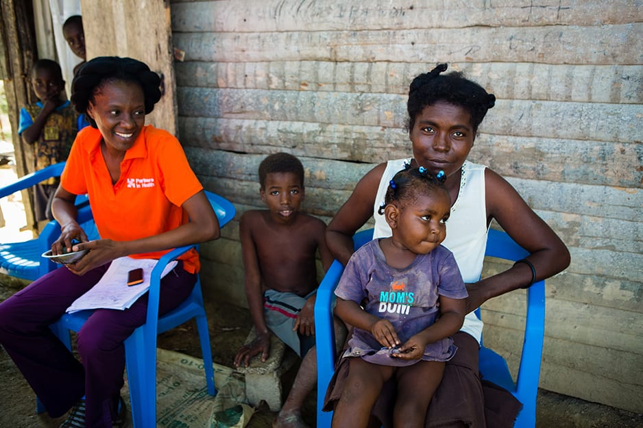 Ms. Colin Alourdes (left), head nurse of the malnutrition clinic in Lascahobas, is proud of Lunie's progress, from unable to walk to an into-everything toddler.