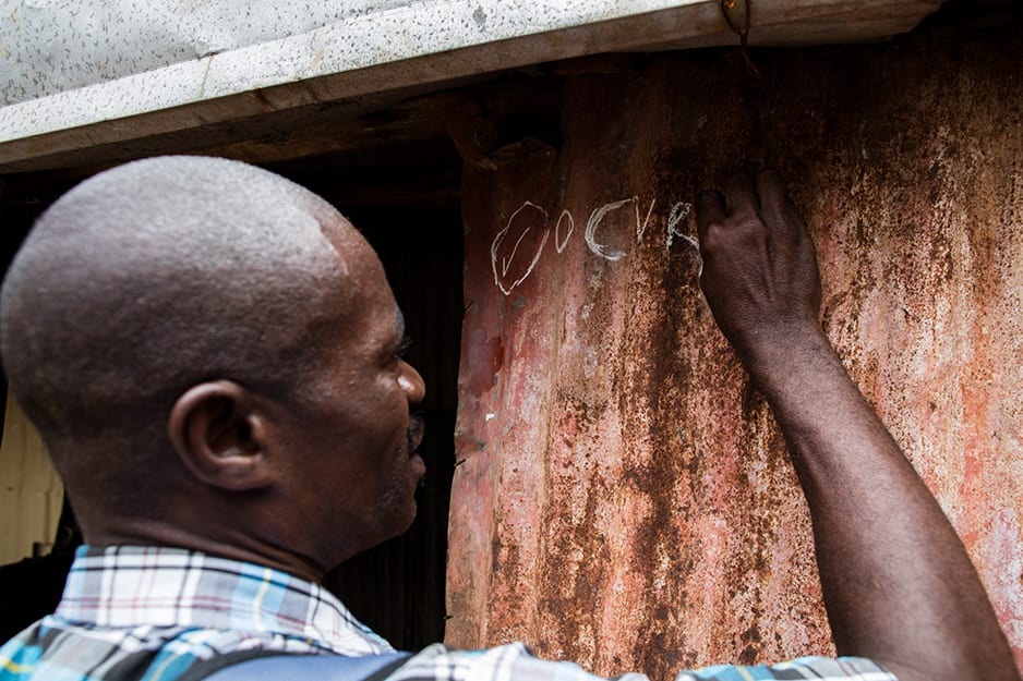 A vaccination team member marks a home in Freetown to show that the family completed the first of two doses.