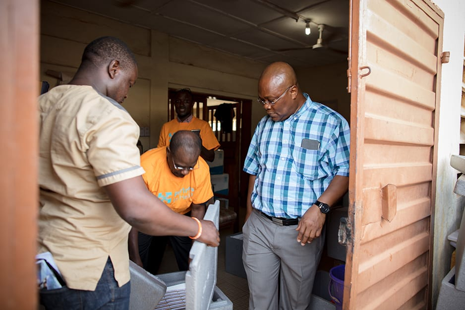 The Ministry of Health and Sanitation's Dr. Dennis Marke, right, an immunization expert, inspects an early shipment of the vaccine.