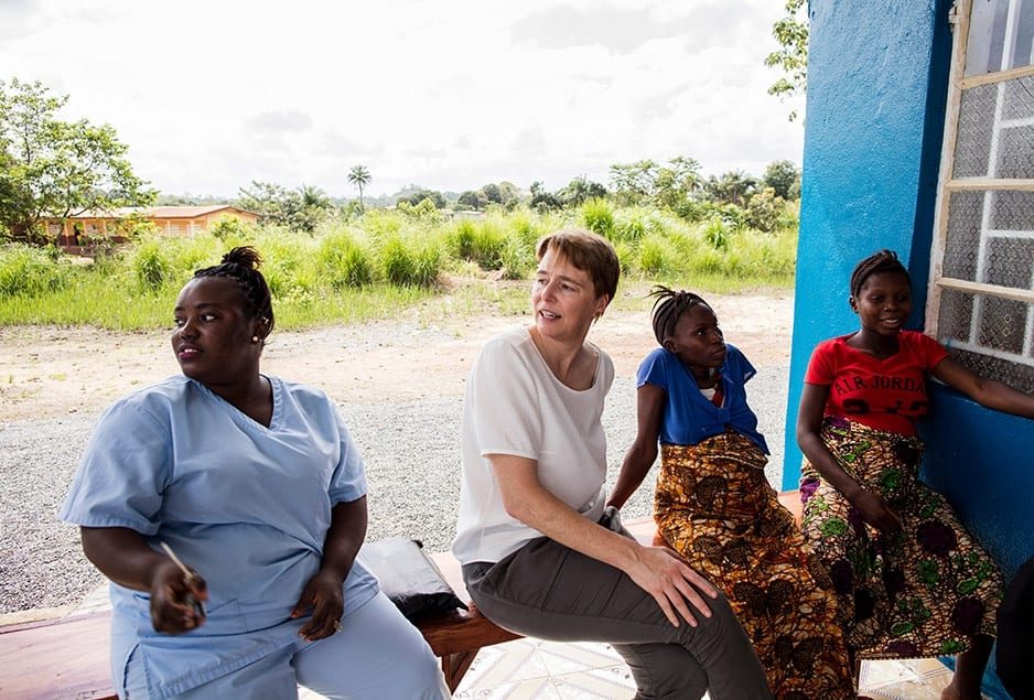 PIH Co-founder Ophelia Dahl (center) and Nurse Ndamba Mansaray (left) visit with Isah Kaimoko (second from right) and Kumba Finohtwo (right), two pregnant women staying at the Wellbody Birth Waiting Home in Kono, Sierra Leone.