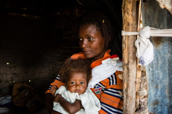 Darius holds her son Stevenson, 6 months, inside their home in Boucan Carre, Haiti.
