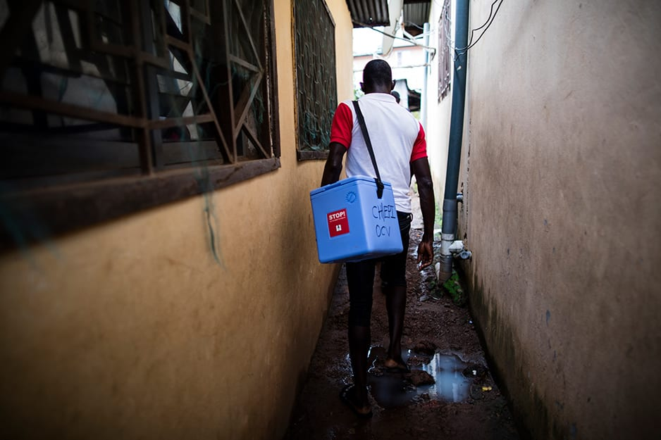 A vaccination team member shoulders a cooler of the temperature-sensitive medicine.
