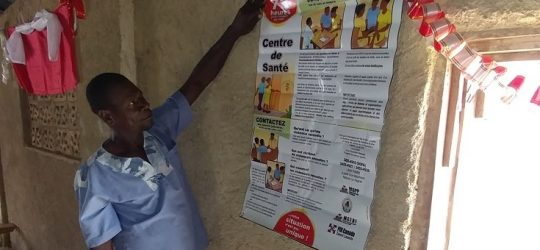 A male GBV Committee member shows a poster on GBV