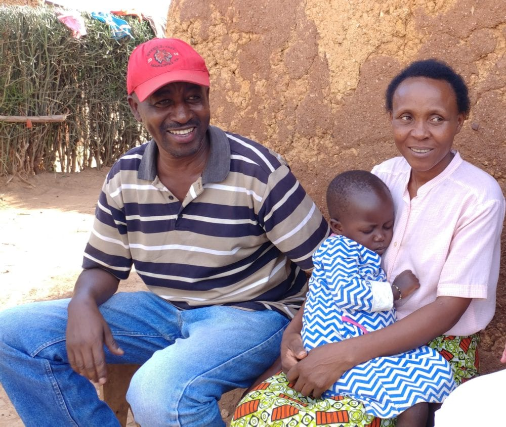 Agnes and her daughter Aline sit with Sebu Gaston, PIH's Agriculture Program Coordinator during a home visit