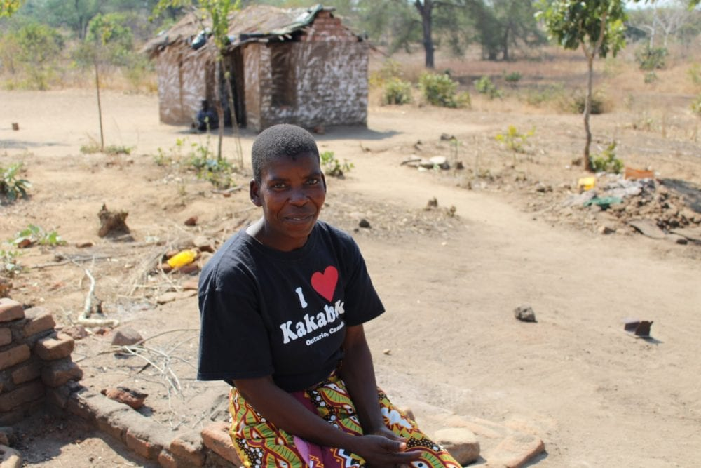 Idah sits smiling with a small house in the background
