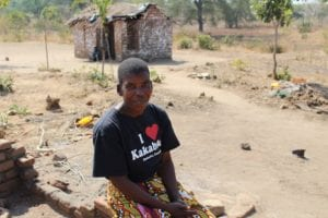 Idah sits smiling with a small house in the background.