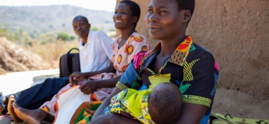 Agnes Paulo sits with her 6-weeks-old son Ulemu outside their home. Two PIH community health workers sit beside her.