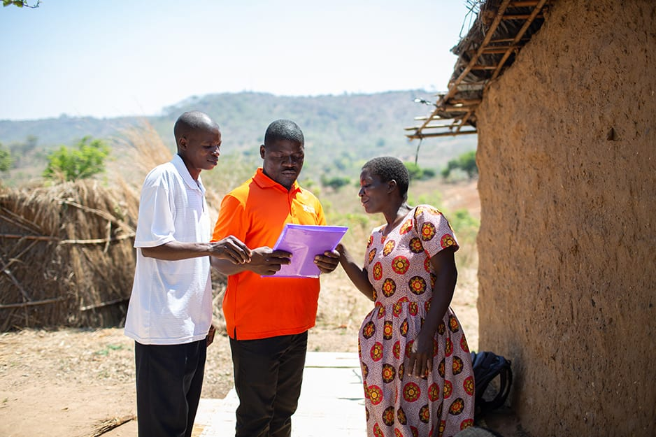 Three PIH community healht worker staff stand reviewing health documents.