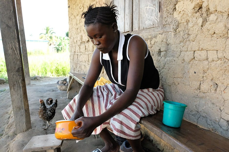 Fanta Karoma sits outside her home preparing breakfast