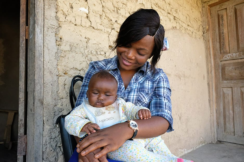 Zainab Kalokeh, a midwife who cared for the young mother, holds Karoma's son during a regular visit.