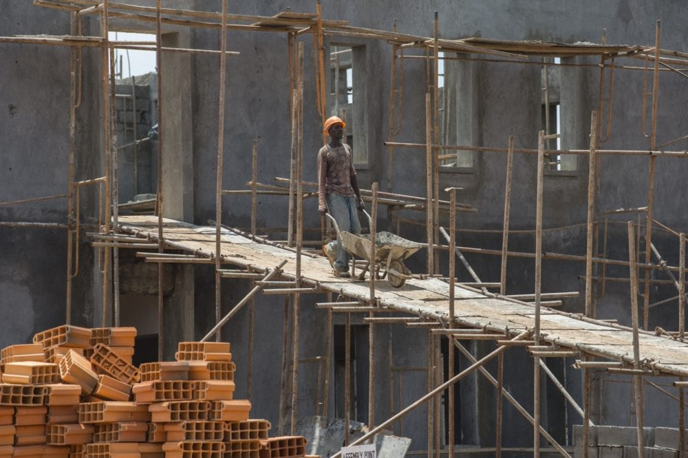 A construction worker moves a wheelbarrow through the UGHE construction site