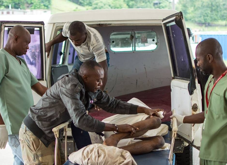 Staff help move a patient from an ambulance in Haiti