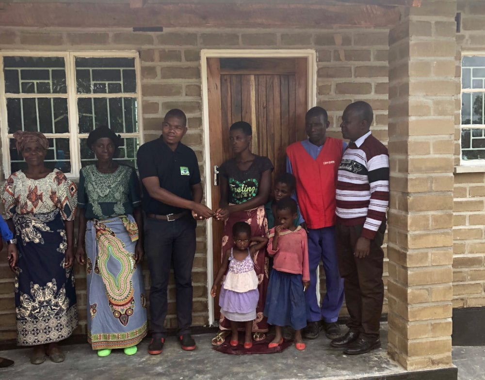 Rose, her children, PIH staff and community members stand in front of a newly constructed brick house