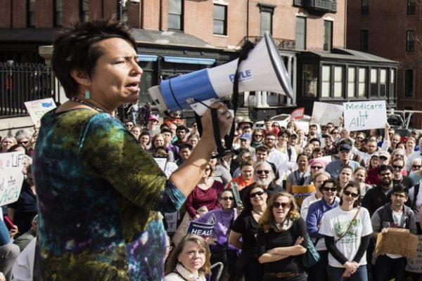 Dr. Joia Mukherjee stands in front of a crowd speaking into a megaphone