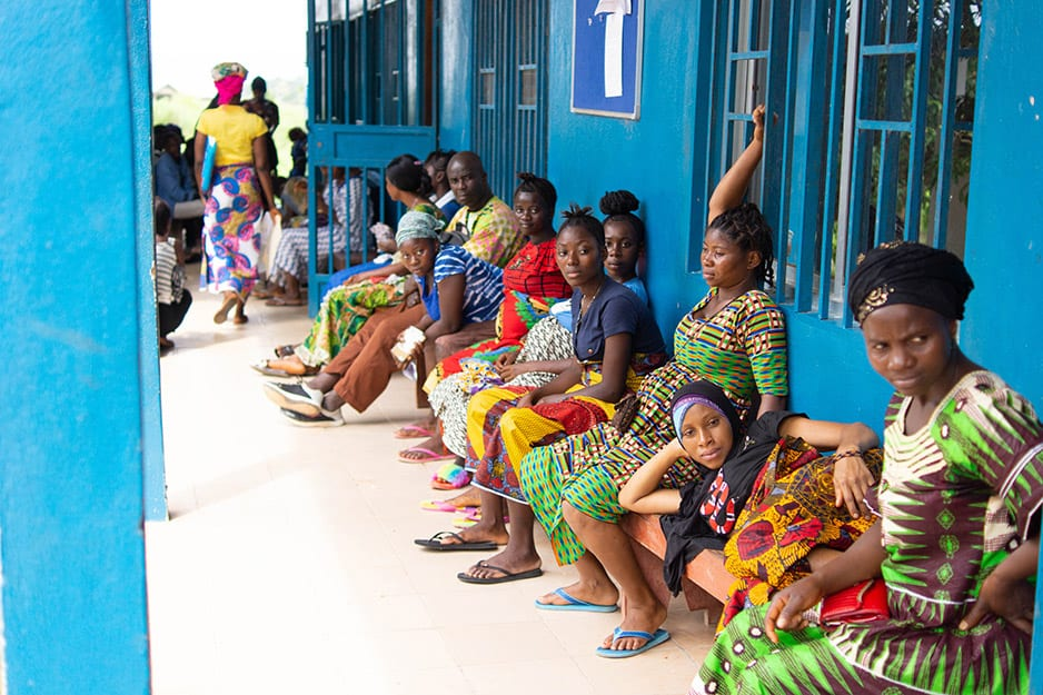 A row of women sit on a bench along the blue walls of the clinic