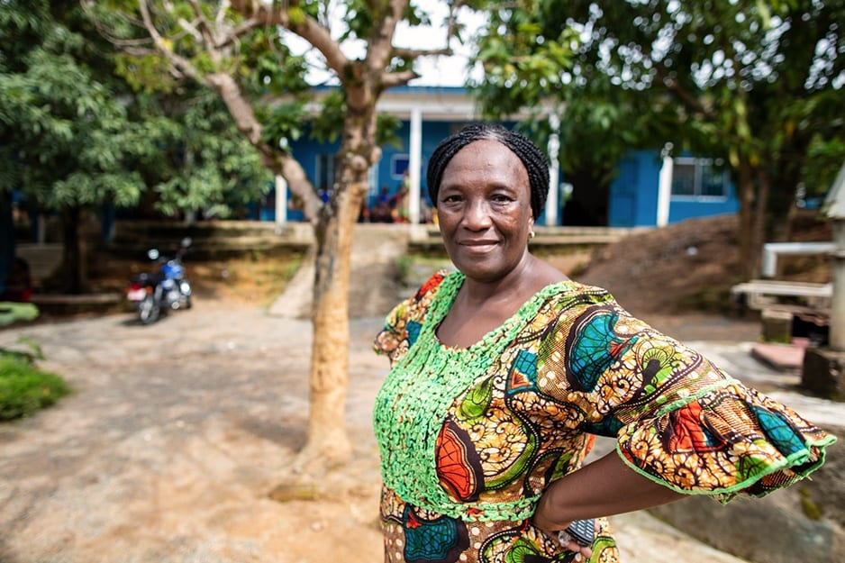 Gladys, wearing a colourful print dress, stands smiling in front of Wellbody Clinic