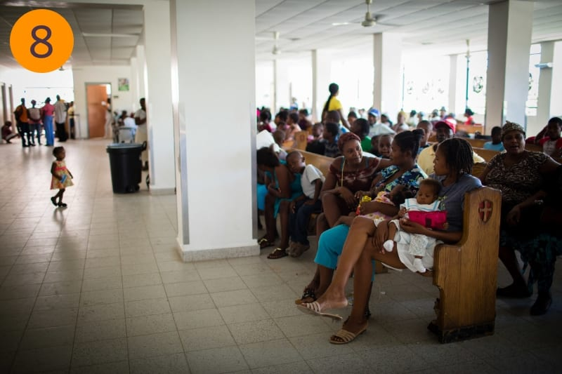 A large group of people sit in rows on benches in the waiting room of the hospital