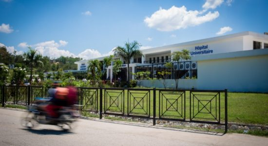 A motor bike drives past the front of University Hospital in Mirebalais