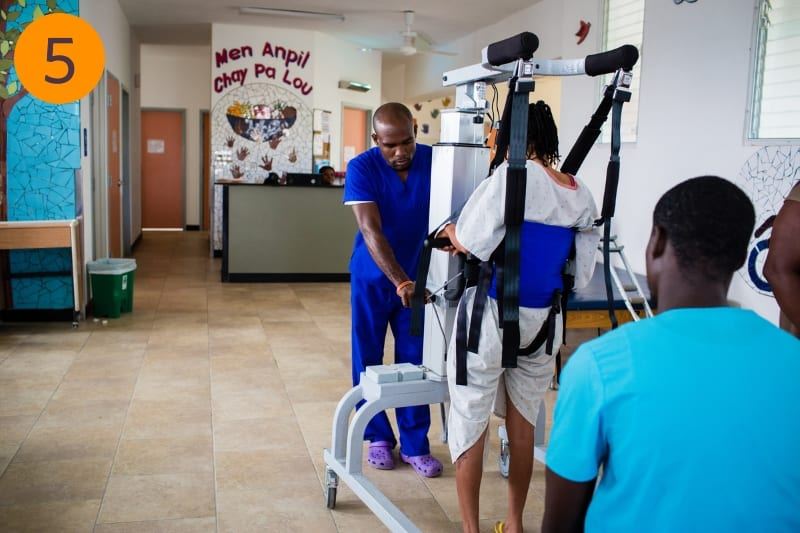 Rehabilitation staff work with a patient to help them walk