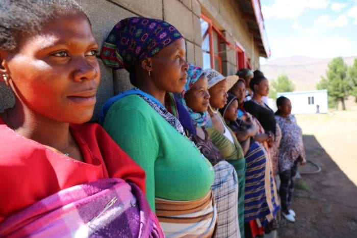 A line of women stand along the outside wall of a clinic