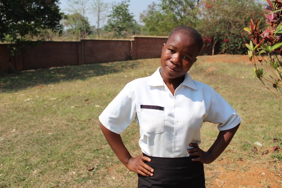 17-year-old Blessings Henry stands in her school uniform