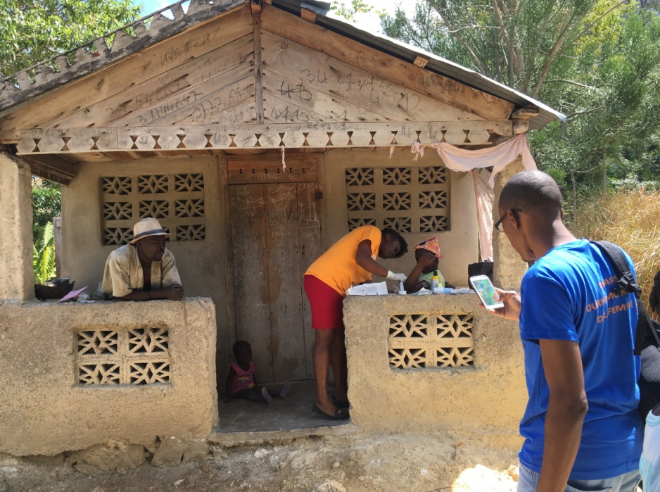 A PIH nurse and social worker visit a family outside the front door of their home