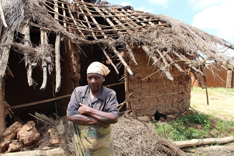 A woman stands with her arms crossed in front of a collapsed section of her home