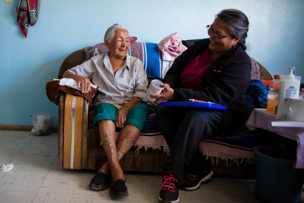 A community health worker sits with an elderly patient on their couch during a home visit