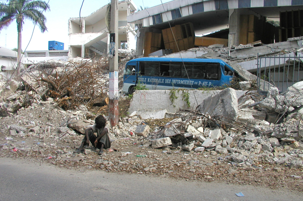 A boy sits in the rubble of a collapsed building with a bus in the background