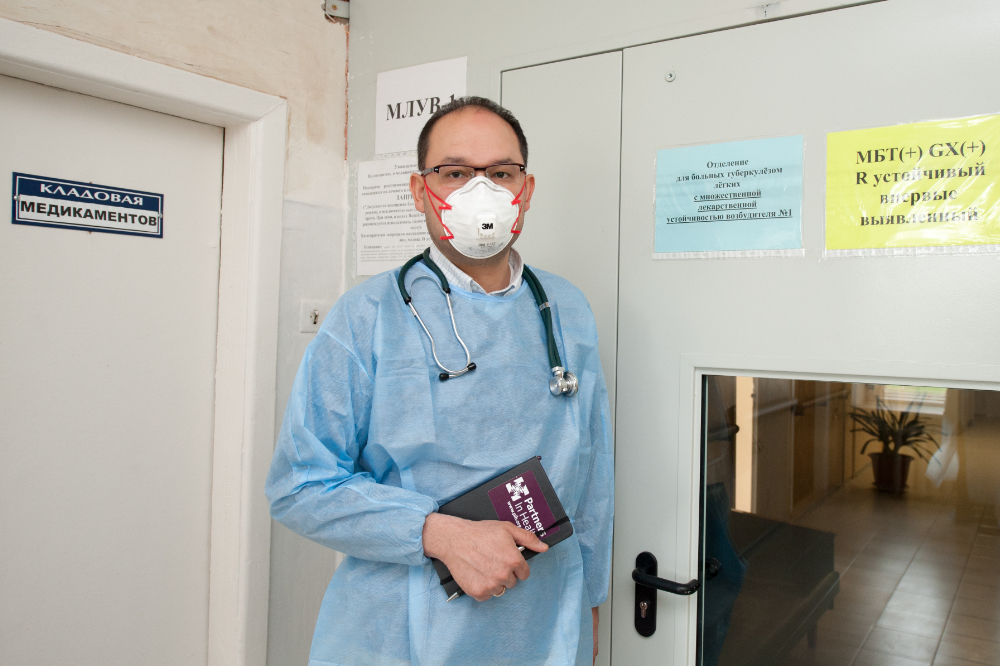 A male doctor stands holding a notebook and wearing a surgical mask