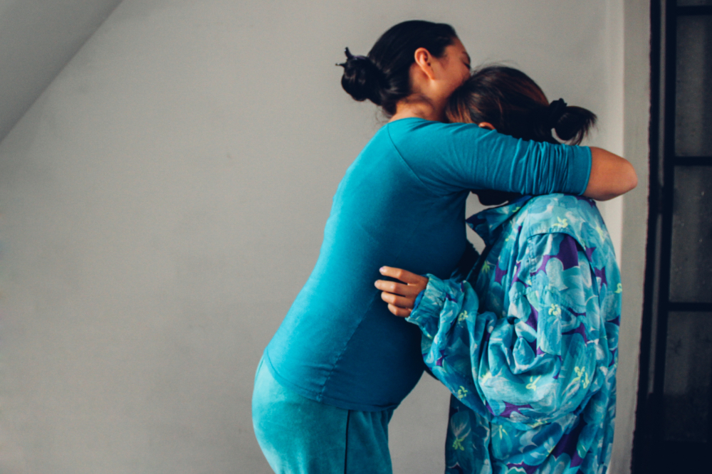 Two women stand hugging