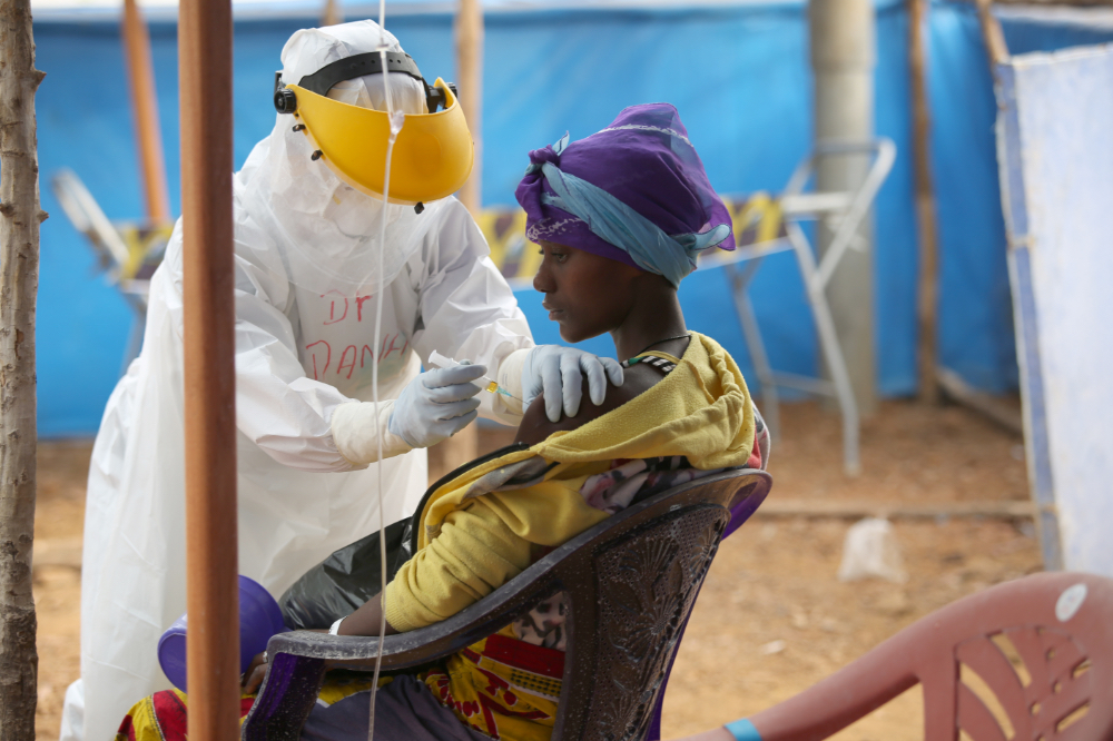 A PIH staff member cares for a patient at an Ebola treatment centre