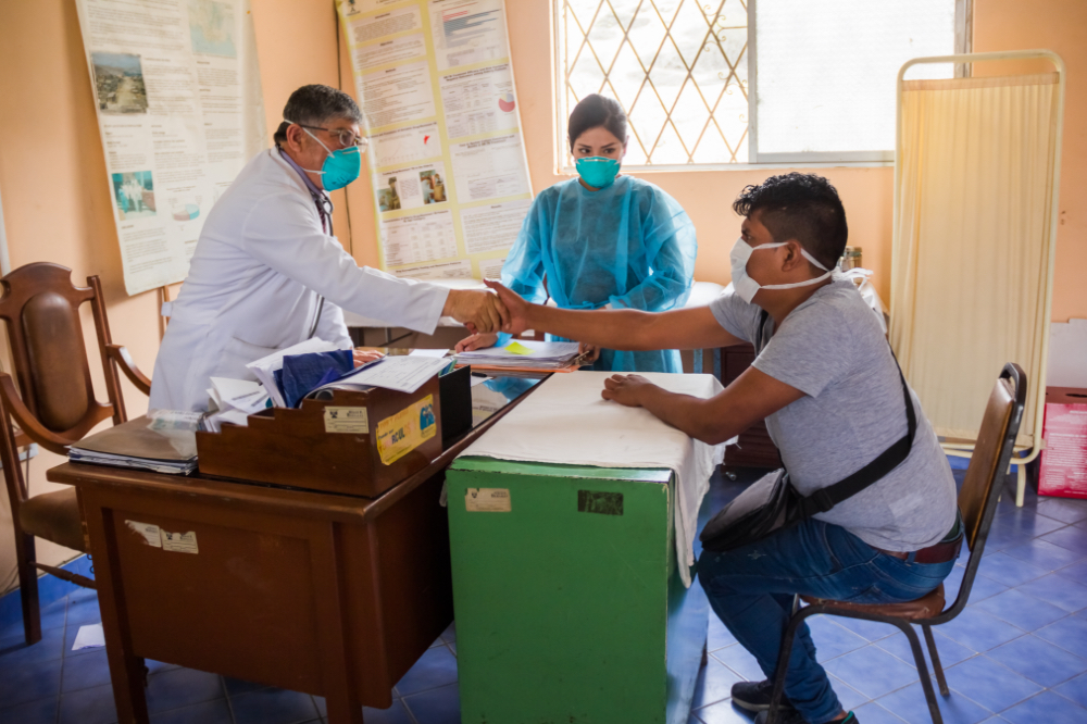 A doctor and patient shake hands over a desk