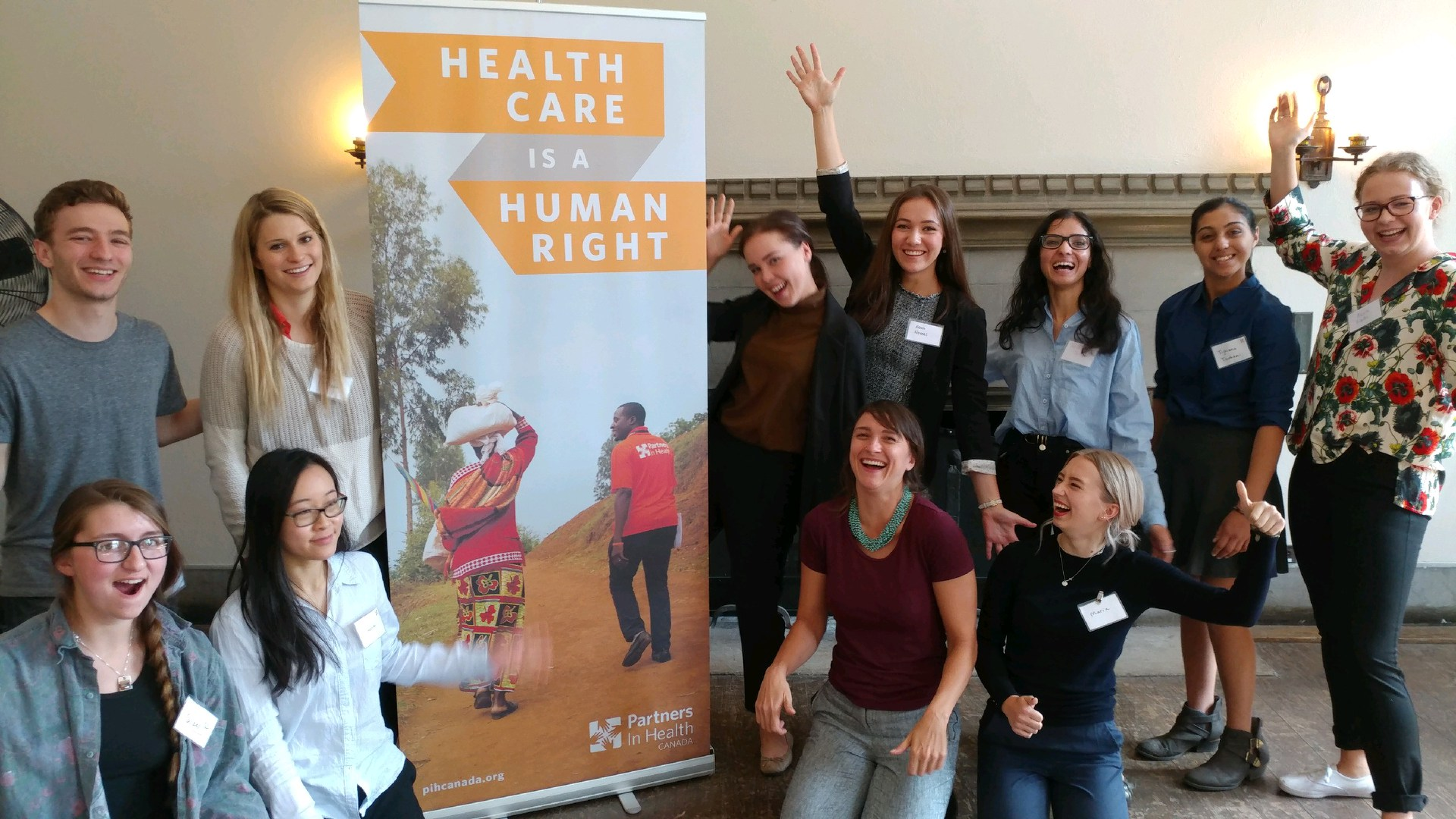 SPIHC members stand near a PIH Canada banner at a student conference