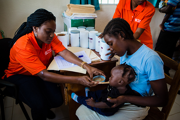 A PIH staff member feeds Nourimanba to a young child who is sitting on their mother's lap