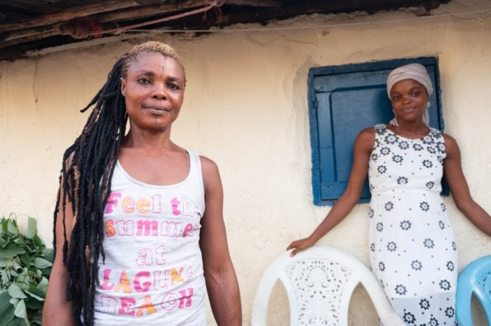 Mariama stands with her daughter outside their home