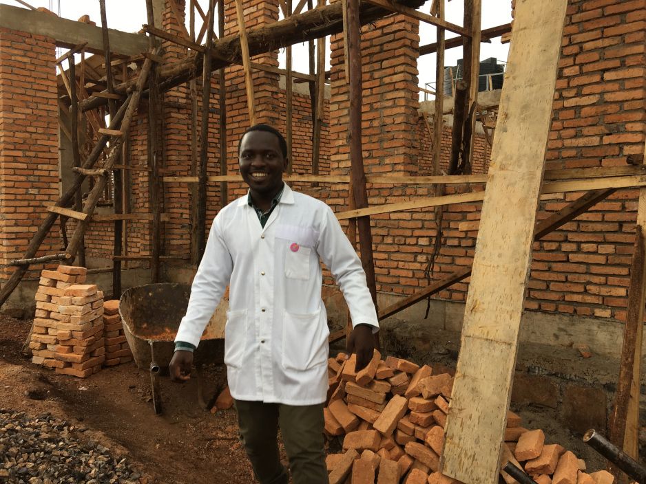A nurse stands in front of a partially constructed building which, when finished, will be a pediatric clinic