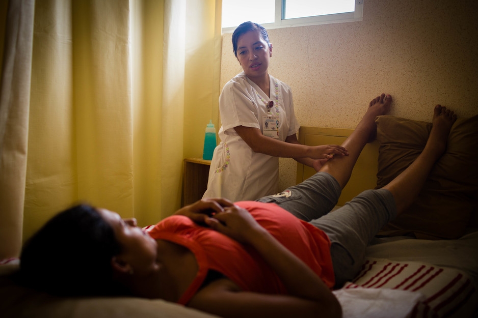 Alma Rosa Valentin, an obstetrics nurse, examines the swollen legs of a patient e Casa Materna in Jaltenango.