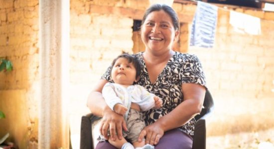 Olga Veronica Roblero sits outside their home holding her three-month-old son, Omar,