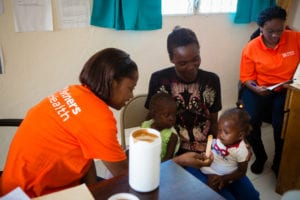 A PIH nurse feeds a child Nourimanba at a malnutrition clinic in Haiti
