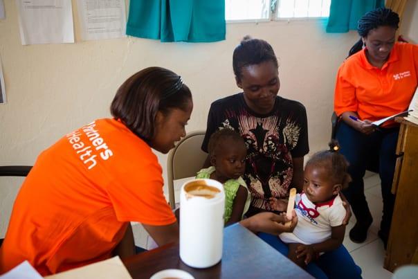 A PIH nurse feeds a child Nourimanba at a malnutrition clinic in Haiti