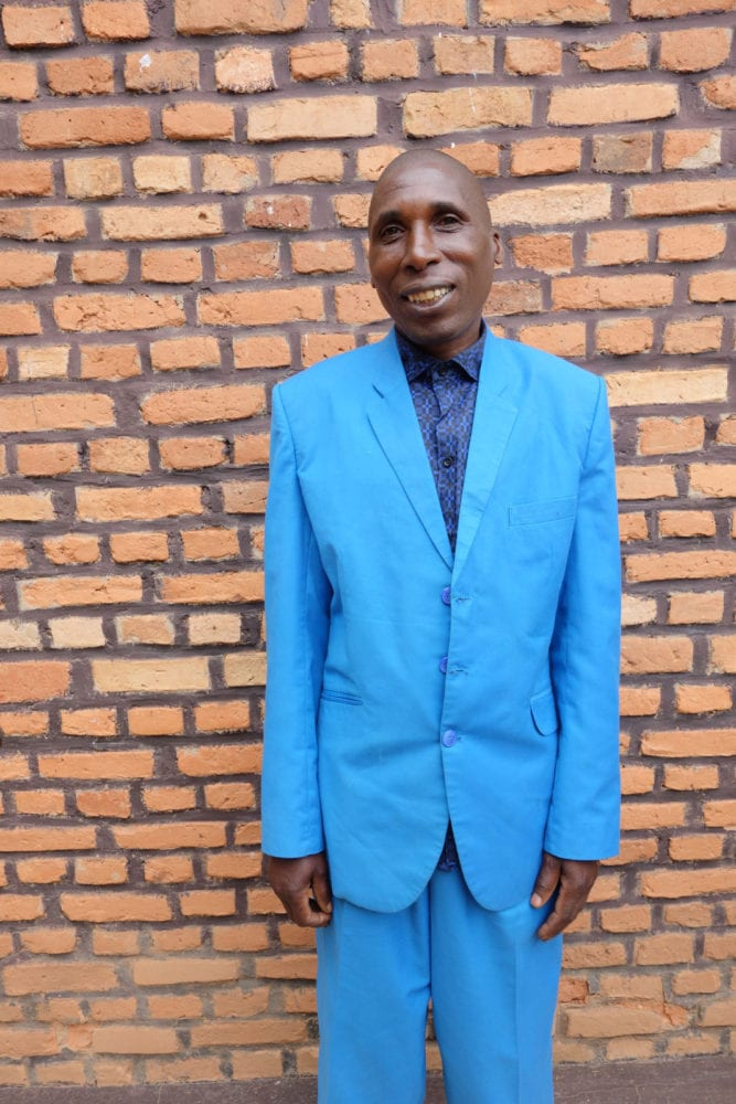 Claver Mugenzi stands wearing his blue suit