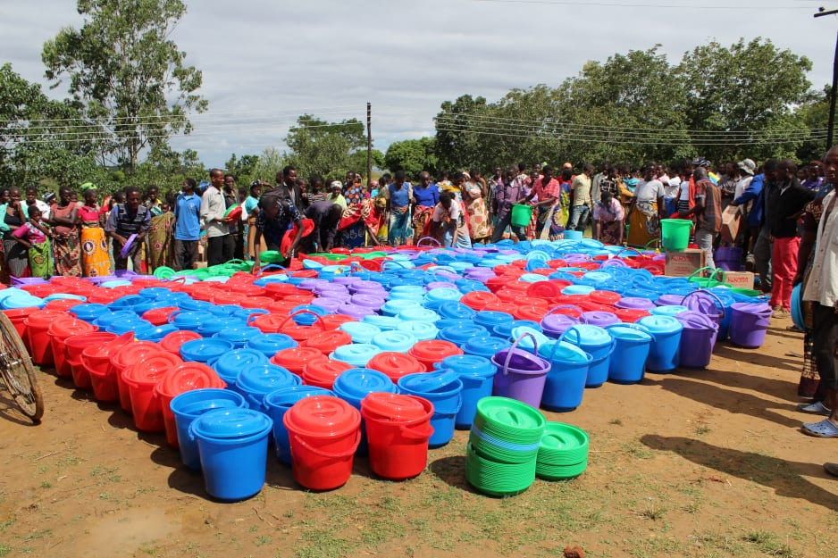 Lines of people stand around buckets of supplies that are to be distributed to flood victims