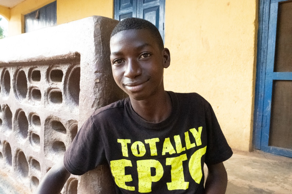 Mondeh Mansaray, 14, sits outside his home in Sierra Leone
