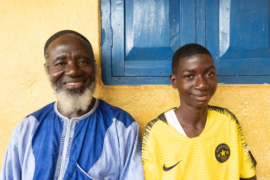 Mondeh and his father, Abubakar Mansaray, sit smiling outside their home in Sierra Leone