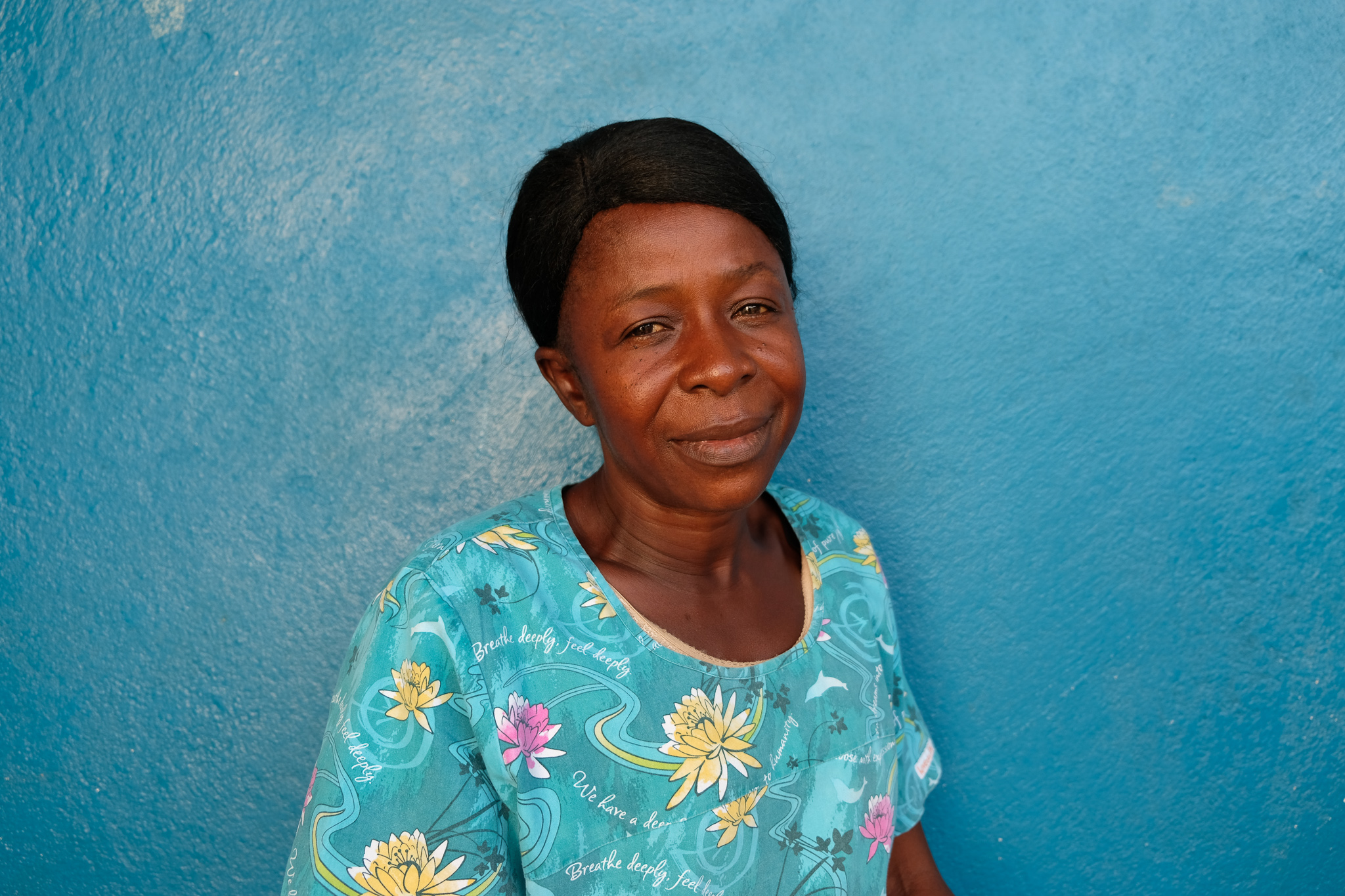 Regina Korgbendeh, a 48 year old traditional birth attendant stand smiling against a blue wall,