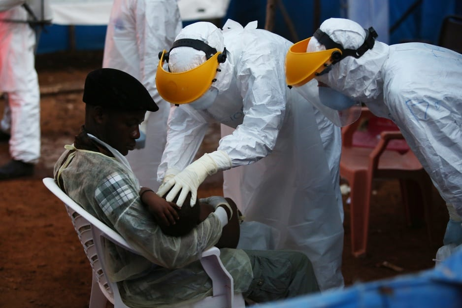 Two clinicians in protective gear check on a young patient in an Ebola Treatment Unit in Sierra Leone in 2015