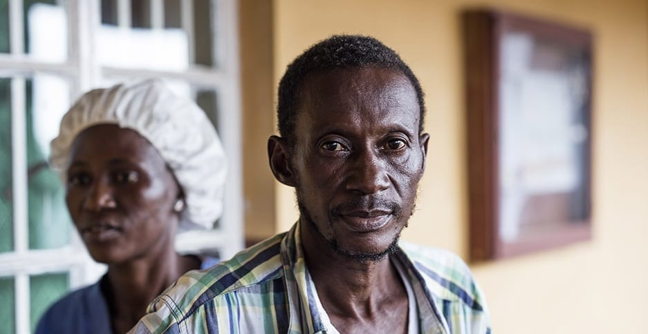 Joseph, a TB patient in Sierra Leone, stands outside the PIH clinic