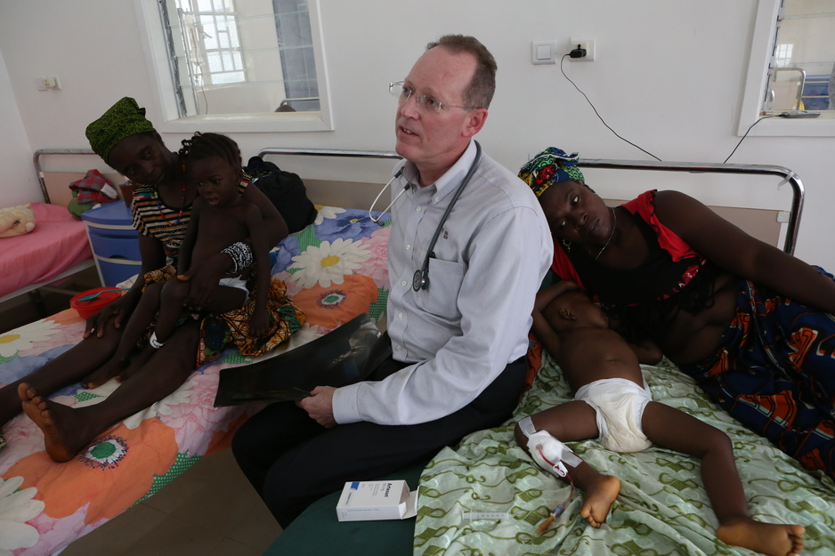 Dr. Paul Farmer sits on the side of a bed while visiting patients in a pediatric ward